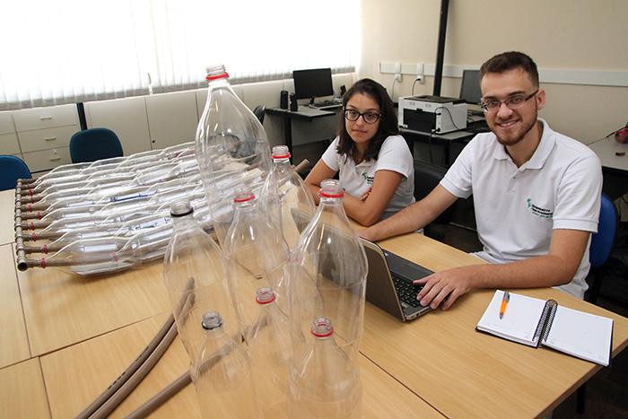 Fernanda Deister Moreira e Rafael Macedo de Oliveira trabalham em aquecedor solar feito com material reciclável (Foto: Fernando Priamo)